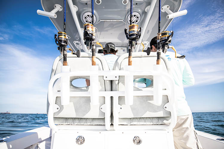 Picture of spinning reels in rod mounts on boat.