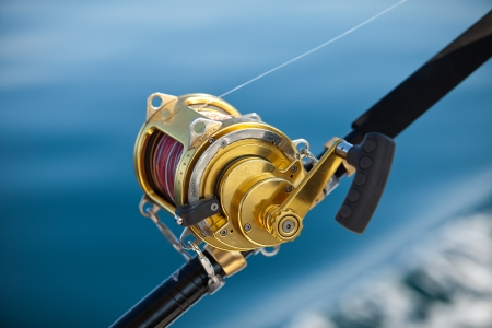 Picture of baitcaster reel in hand.
