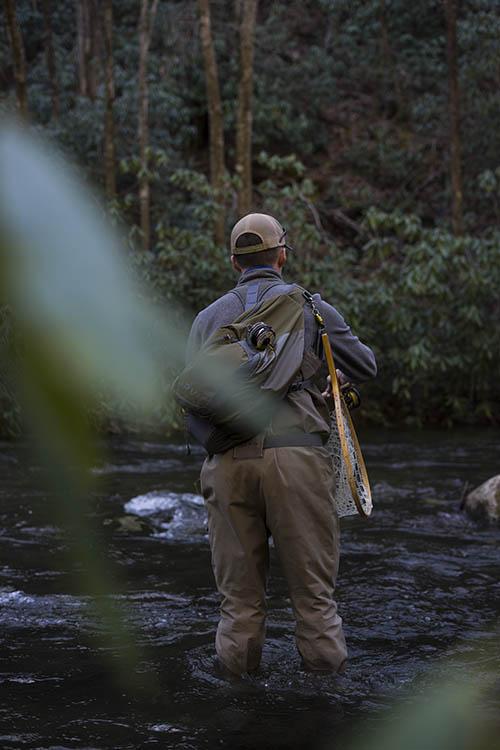 Man in creek fly fishing.