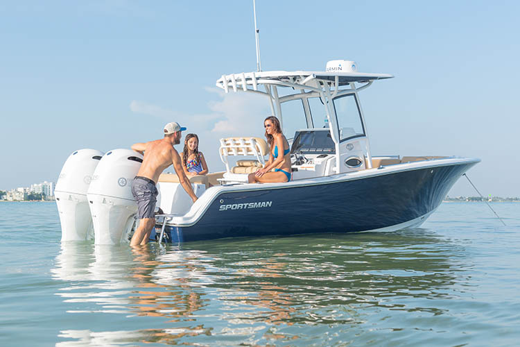 Family pictured at a sandbar with the dad boarding the boat from the rear while anchored.