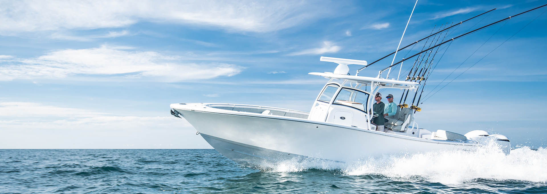 Open 312 with a gray hull bottom color running through open ocean with 2 anglers on-board.