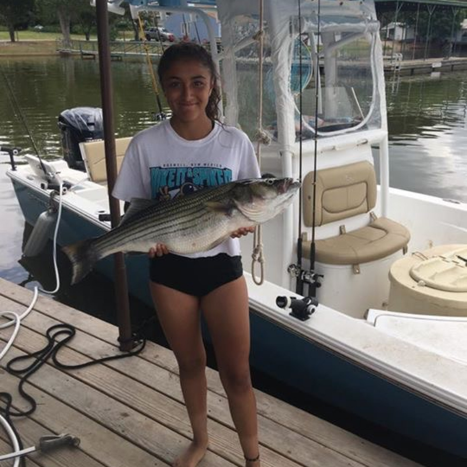Title: Young lady with striper - On board their Sportsman Masters 247 Bay Boat - Location: Possum Kindon Texas. Participating in the Photo Contest #SportsmanFebruary2018